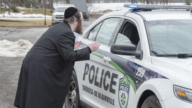 Un homme vêtu d'un costume traditionnel discute à bonne distance d'une voiture de police.