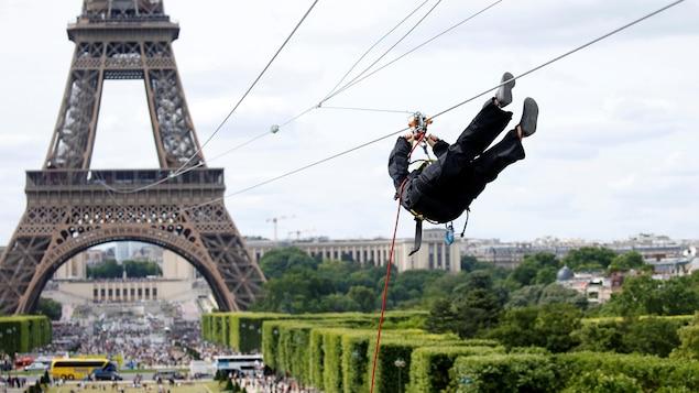 Un homme est suspendu au câble  de la tyrolienne de la tour Eiffel. Le câble de la tyrolienne part du deuxième palier de la tour. Le parcours est de 800 mètres et s'arrête près du Mur de la Paix?