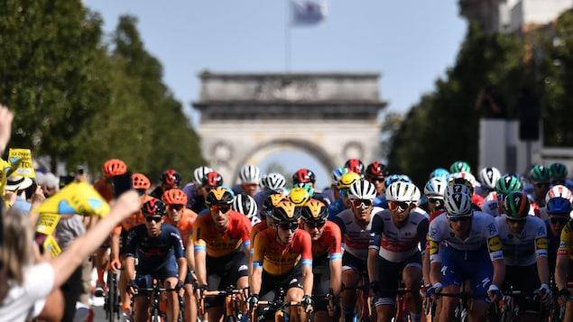 Des dizaines de cyclistes roulent devant des partisans.