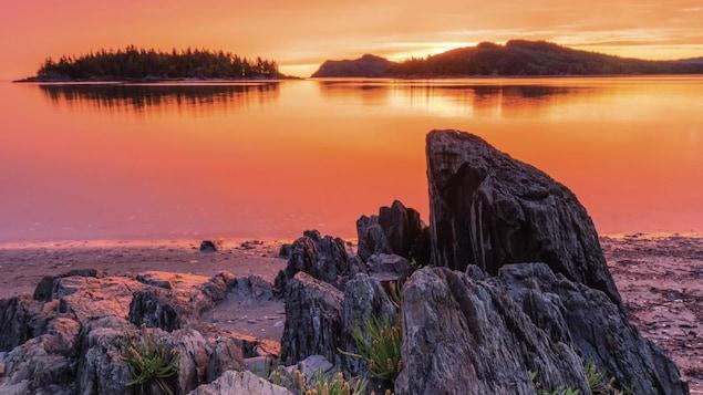 La couverture du guide touristique officiel 2020-2021 Bas-Saint-Laurent. Un  coucher de soleil se cache derrière une île.