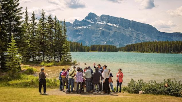 Des touristes asiatiques visitent le parc national de Banff. Ils se tiennent devant le lac Two Jack. Au loin s'élève le mont Rundle.