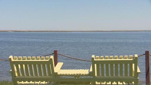 Deux bancs devant une petite baie.