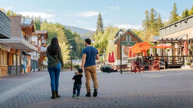 deux parents et un jeune enfant dans une place de petite ville.