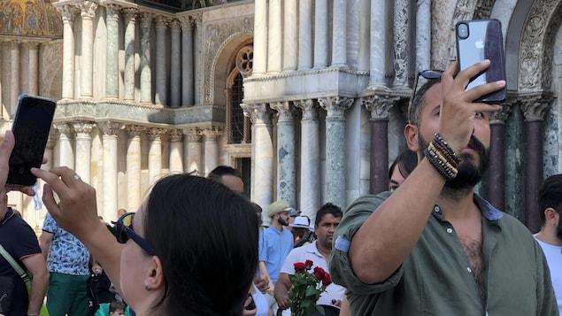 Des touristes brandissent leur cellulaire pour prendre quelques clichés.