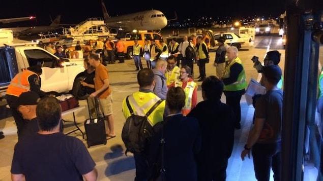 Des touristes canadiens de retour au pays sur le tarmac de l'aéroport Pearson