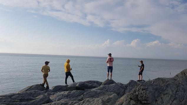 Des touristes pêchent sur le bord du fleuve à Rivière-du-Loup.