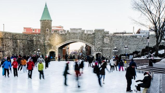 Des patineurs sur la glace de la place D'Youville