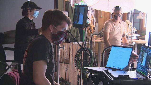 Trois personnes travaillent sur un plateau de tournage en portant un masque.
