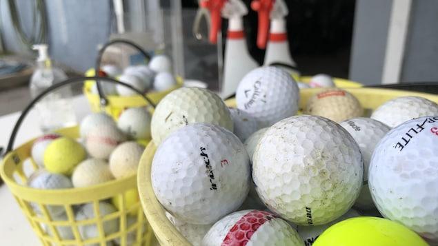 Des paniers de balles de golf et des bouteilles de désinfectant.
