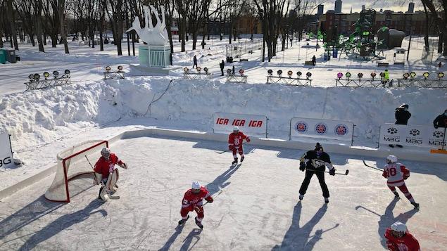 Les joueurs jouent sur la patinoire extérieure, le parc boisé derrière eux.