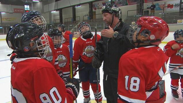 De jeunes hockeyeurs qui écoutent leur entraîneur.