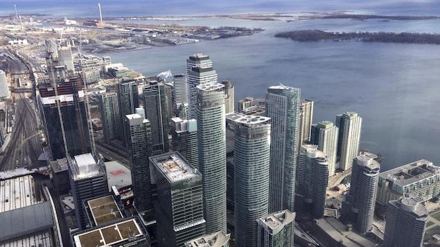 Vue en hauteur du centre-ville de Toronto l'automne, avec de nombreux gratte-ciels et en arrière-plan, le lac Ontario.