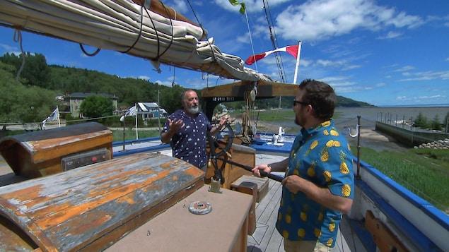 Marc-André Boivin interroge un homme sur le pont d'un voilier désaffecté.