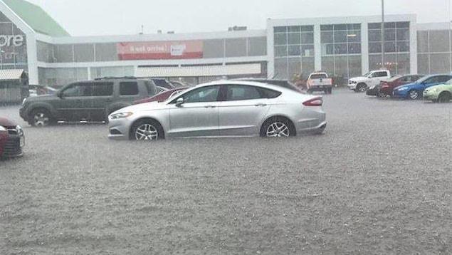 Des voitures sous la pluie garées devant le Superstore ont de l'eau jusqu'à la carrosserie.