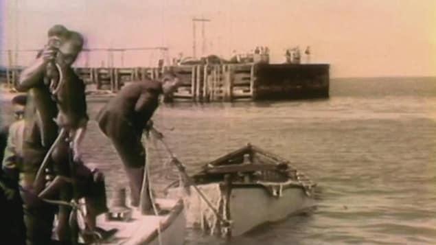 Photo d'archives d'hommes ramenant un bateau vide vers le quai.