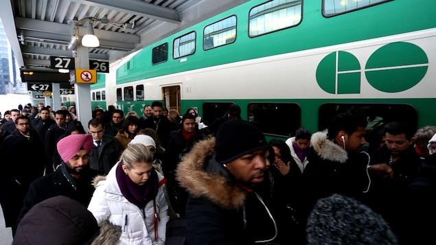 Des usagers dans une station sortent d'un train GO.