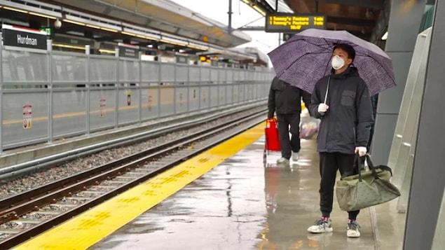 Un homme avec un parapluie et portant un masque attend le train.