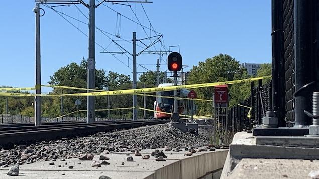 Un train sur rail arrêté et des bandelettes jaunes indiquant qu'il ne faut pas s'approcher.