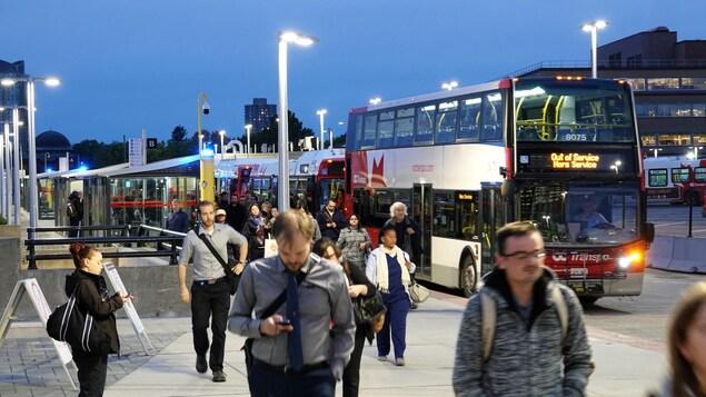 Des gens quittent l'autobus pour se rendre à une gare du train léger