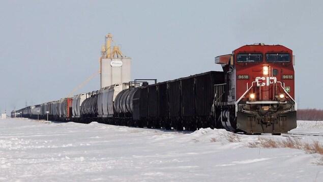 Un train de marchandises en hiver prés d'un silo à grains.