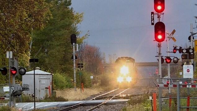 Le train se dirige vers un passage à niveau en fin de journée.