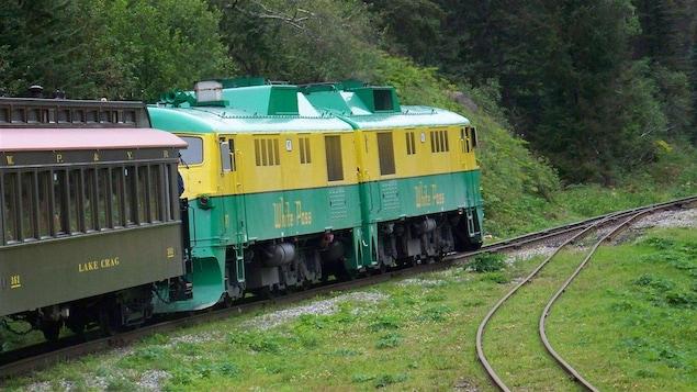 Une locomotive d'un train touristique tire des wagons vers le col de White Pass