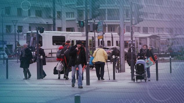 Des piétons traversent des voies de tramway