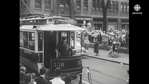 Tramway circulant sur une rue bondée de Montréal.