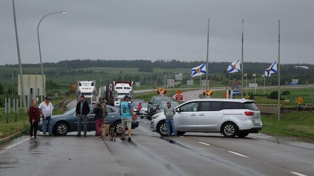 Deux voitures et des manifestants bloquent la route.
