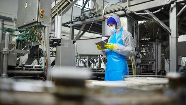 Un travailleur d'usine manipule une tablette informatique.