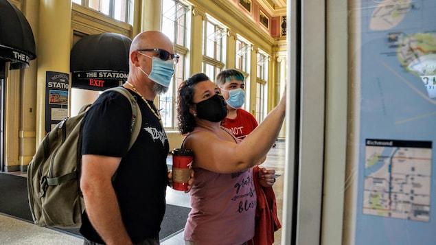 Trois personnes masquées achètent des billets de transport à un distributeur.
