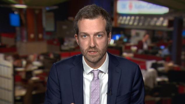 Un homme barbu s'exprime face caméra, il est en costume et porte une cravate.