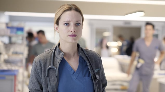 La jeune femme est habillée d'un sarrau bleu et d'un gilet gris.