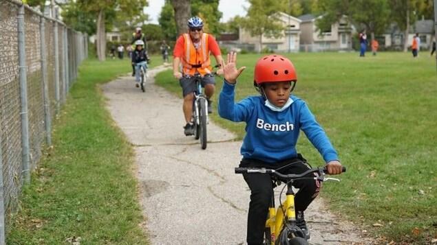 Des élèves à vélo accompagnés d'adultes sur une piste cyclable.