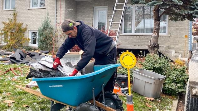 Un homme ramasse du bardeau d'asphalte.