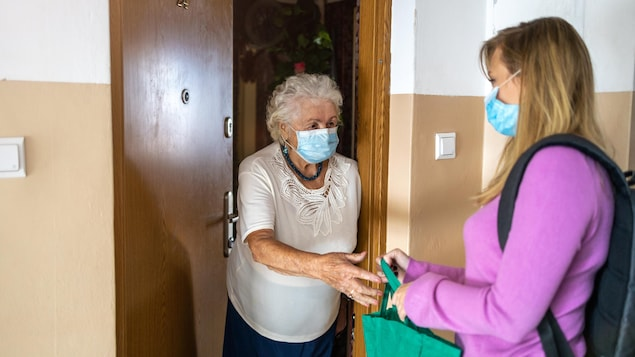 Une travailleuse sociale vient porter des provisions à une femme âgée qui ouvre sa porte.