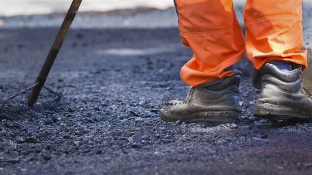 Un travailleur en train de poser de l'asphalte.