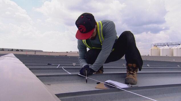 Un travailleur de l'énergie solaire sur un toit.
