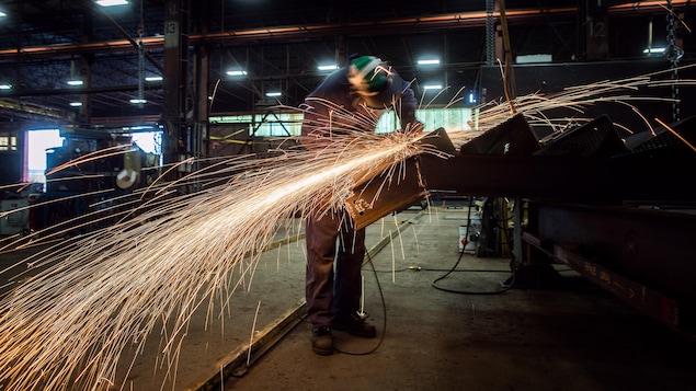 Un ouvrier se sert d'une meuleuse.