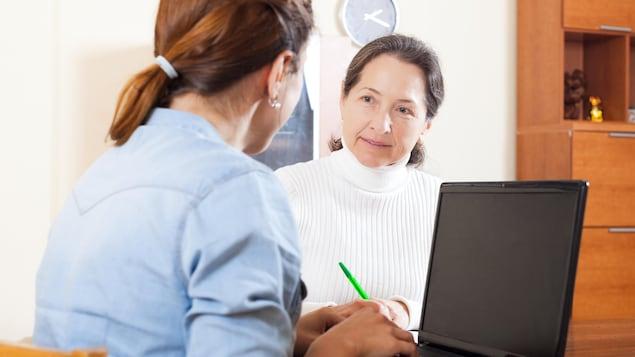 Une femme parle à une autre femme qui écrit à l'ordinateur.