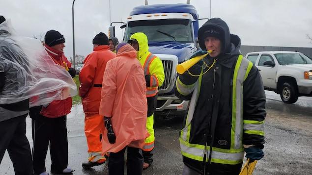 Des manifestants devant un camion-remorque à l'arrêt