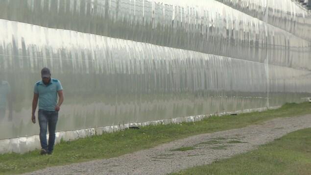 Un homme marche à côté d'un grand mur transparent qui semble être en plastique.