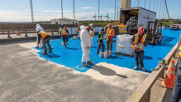 Des ouvriers en tenue de travail appliquent une couche de couleur bleue sur un tronçon de route.