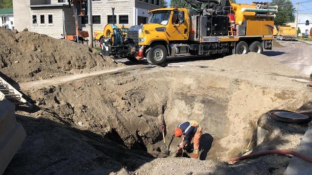 Un travailleur s'affaire dans un trou creusé par une pelle mécanique.