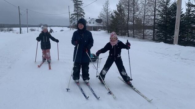 Des élèves et leur enseignant en ski de fond sur un chemin enneigé.