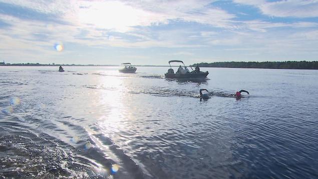 Des nageurs dans l'eau, suivis par quelques bateaux.