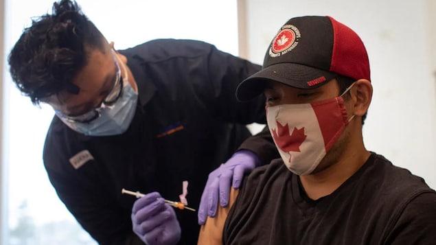 2021 年 5 月 28 日,38 岁的加拿大队轮椅橄榄球 ( wheelchair rugby)运动员 Travis Murao 在多伦多接种第二剂辉瑞 - BioNTech COVID-19 疫苗。