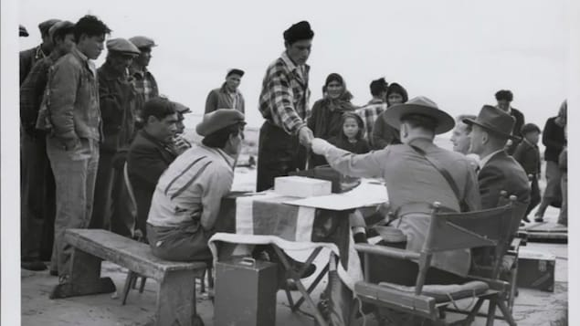 A Dene man accepts money from a fully uniformed Mountie seated behind a table draped with a British flag in Yellowknife. Food and money were distributed in communities after — and sometimes before — Treaty 11 was signed.