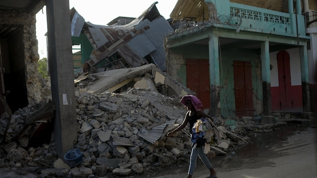 A woman walks past a collapsed building in Jeremie, Haiti, Wednesday, Aug. 18, 2021, four days after the city was struck by a 7.2-magnitude earthquake. (AP Photo/Matias Delacroix)
