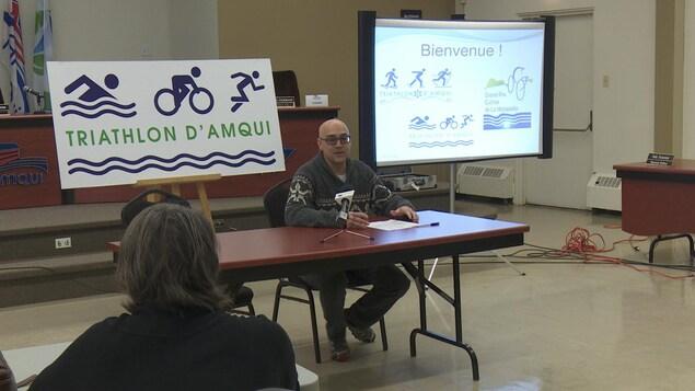 Homme assit à une table devant des panneaux : Triathlon d'Amqui